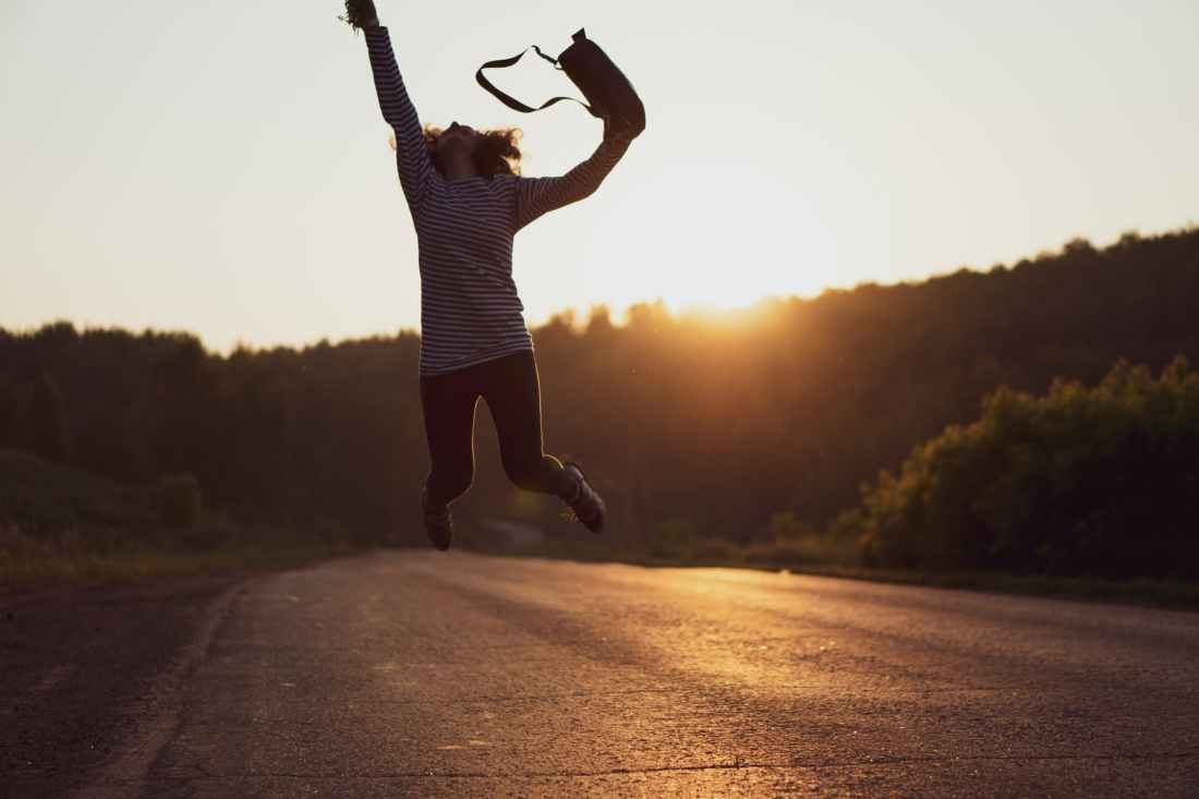 woman jumped on gray asphalt road